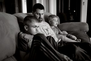 Ryan Kapes, 11, left, with his dad Carl and brother Brayden, 8, watch The Backyardigans at their home in Wilmington, Delaware. Ryan has Sanfilippo Syndrome, a genetic disease that attacks the central nervous system. Most children with the condition die before the age of 20.